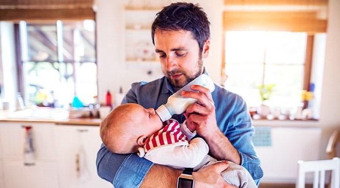 Padre dando biberon hijo